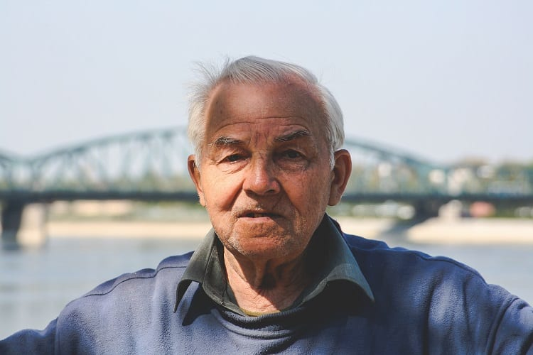 old man with bridge in background